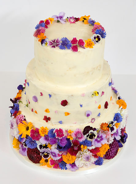 A 'Colour Burst' of Fresh Edible Wild Summer Flowers, covering a Buttercream Iced Wedding Cake, Topped with a Crown.