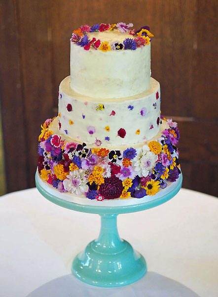 A 'Colour Burst' of Fresh Wild Summer Edible Flowers, covering a Buttercream Iced Wedding Cake, Topped with a Crown.