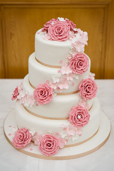 Four Tier Wedding Cake with Champagne Satin Ribbon and a Spiral of Handcrafted Blush Sugar Roses & Flowers.